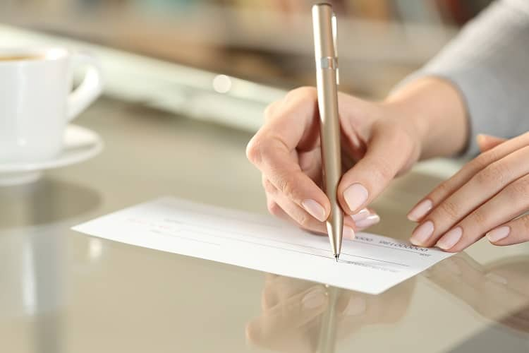 Woman writing check for rent deposit